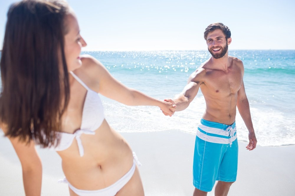 Smiling couple holding hands at the beach